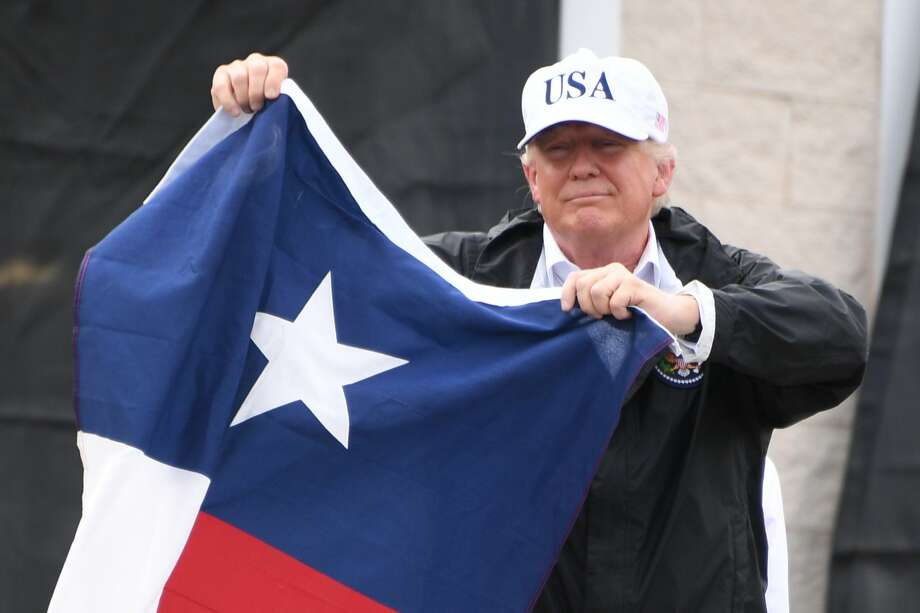President Donald Trump holds the state flag of Texas outside of the Annaville Fire House after attending a briefing on Hurricane Harvey in Corpus Christi on Aug. 29. (Jim Watson/ AFP/ Getty Images) Photo: JIM WATSON, Contributor / AFP or licensors
