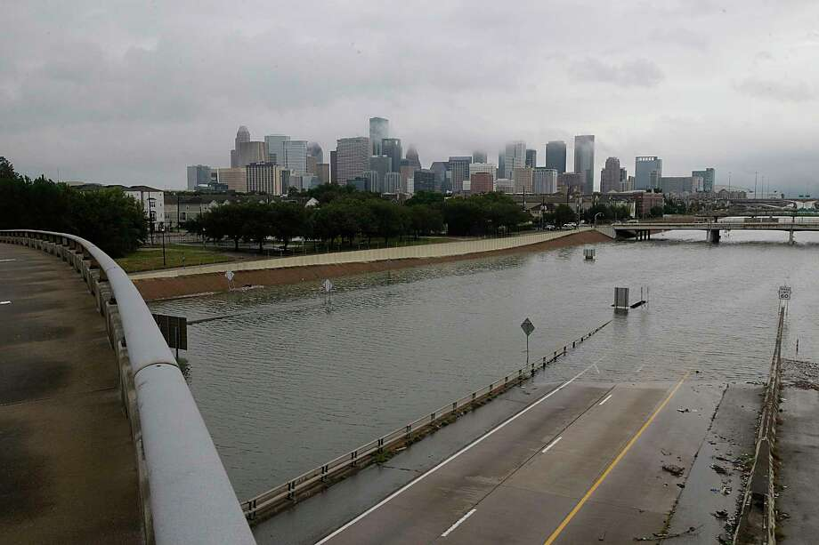 The downtown Houston skyline and flooded Texas Highway 288 are seen Sunday. (Thomas B. Shea/AFP/Getty Images) Photo: THOMAS B. SHEA, Contributor / AFP or licensors