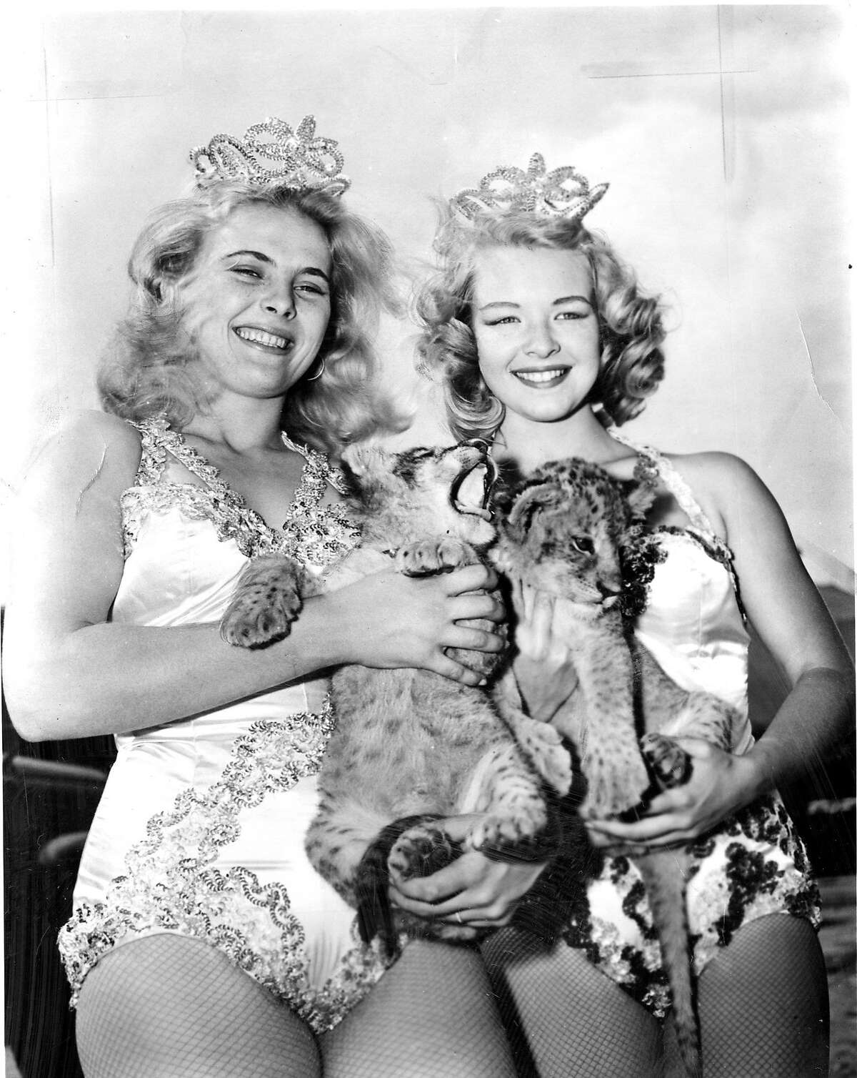 Original caption: Two pretty members of the aerial ballet corps. with the James Bros. Circus are Sally Winslow and Bettie Provine, holding two baby lion cubs recently born on the big show.