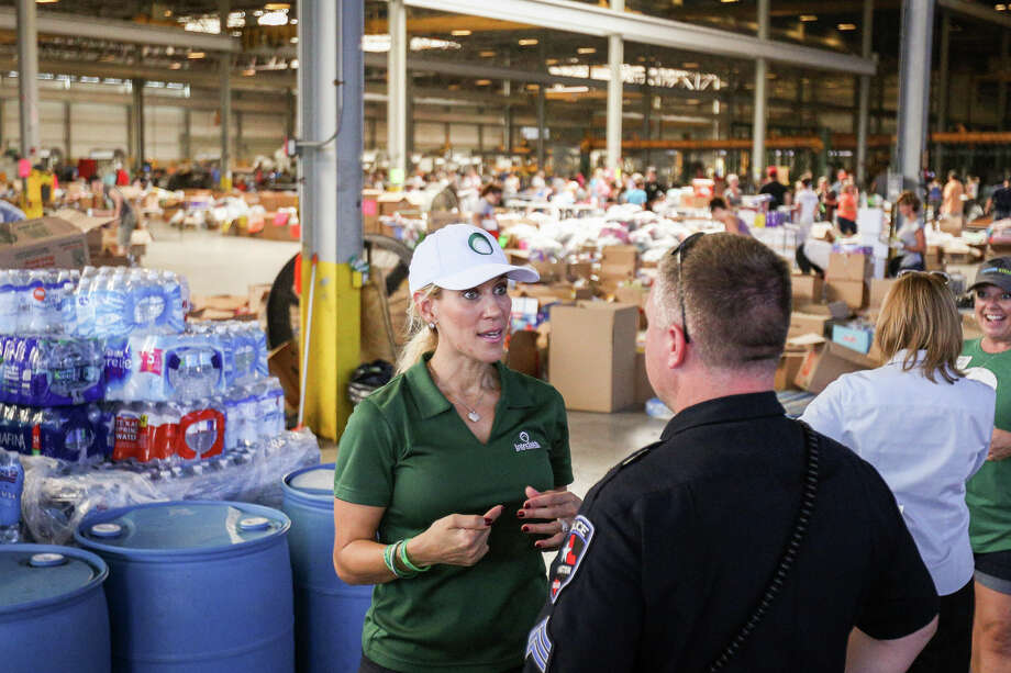 Missy Herndon, Interfaith of The Woodlands President and CEO, speaks with a City of Arlington police officer on Friday, Sept. 1, 2017, at Falcon Steel America's warehouse in Conroe. Falcon Steel America donated the space to serve as a central drop off location for supplies to help Montgomery County residents affected by Tropical Storm Harvey. Photo: Michael Minasi, Staff Photographer / © 2017 Houston Chronicle
