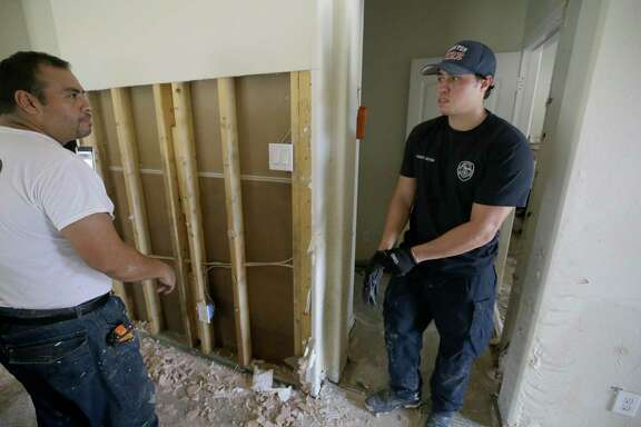 Jesse Morales, left, helps his son, Jordan Morales, a Houston firefighter with Station 9, clean up his flooded home Friday, Sept. 1, 2017, in Spring. He said about 5 feet of water flooded his home in the aftermath of Hurricane Harvey. He does not have flood insurance. ( Melissa Phillip / Houston Chronicle )