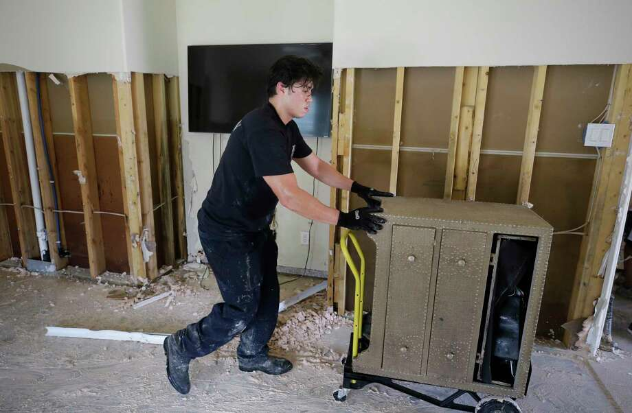 Houston firefighter Jordan Morales cleans up his flooded house in Spring in the aftermath of  Hurricane Harvey. Photo: Melissa Phillip, Staff / © 2017 Houston Chronicle