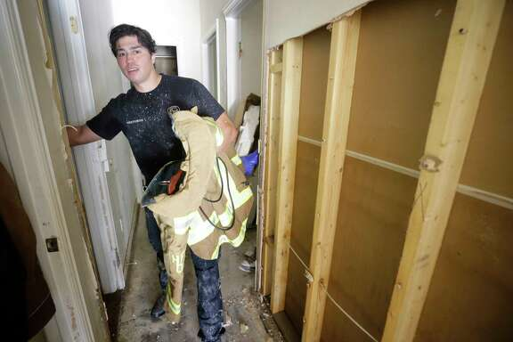 Jordan Morales, a Houston firefighter with Station 9, packs up his bunker coat as he cleans up his flooded home Friday, Sept. 1, 2017, in Spring. He said about  5 feet of water flooded his home in the aftermath of Hurricane Harvey. He does not have flood insurance. ( Melissa Phillip / Houston Chronicle )