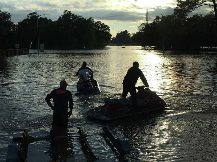 Rescuers Chris Goldman and Bill Slayden used jet skis in a failed attempted to reach an evacuation at the Park Row apartment complex, which anticipated flooding from the Addicks reservoir on Tuesday. Photo: Hunter Atkins / Houston Chronicle