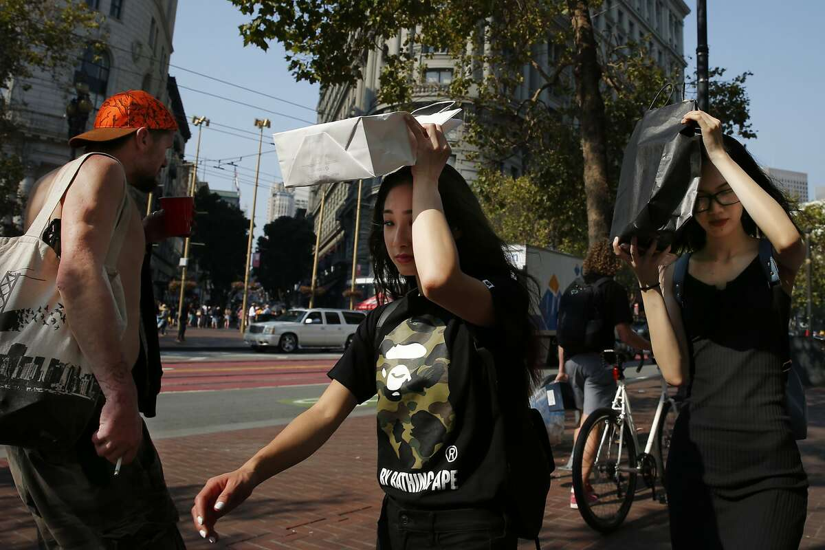 Pedestrians take cover from the sun with their shopping bags along Market Street on Friday, Sept. 1, 2017, in San Francisco, Calif. The National Weather Service issued an excessive heat warning as the San Francisco Bay Area reached temperatures in the upper 90s and some areas surpassed 100 degrees. At its highest ever, San Francisco reached 106 degrees.