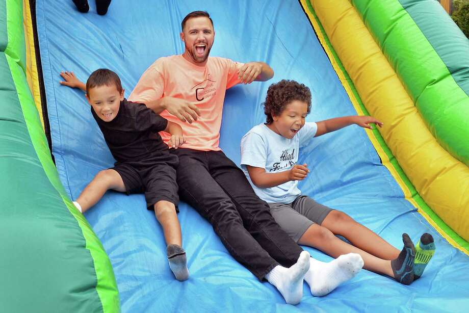 T.J. Czeski, director of Creative Connections Clubhouse, center, tries out the bounce house with Garyn Toledo, 7, and Trace Fulton,9, right, during the first anniversary celebration for the state's first Youth Clubhouse Tuesday August 29, 2017 in Amsterdam, NY.  (John Carl D'Annibale / Times Union) Photo: John Carl D'Annibale / 20041363A