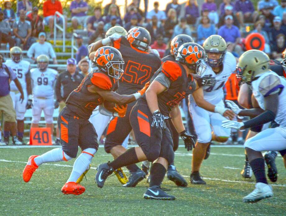 Edwardsville running back Dionte Rodgers, left, runs behind his offensive line during first-quarter action against CBC on Friday.