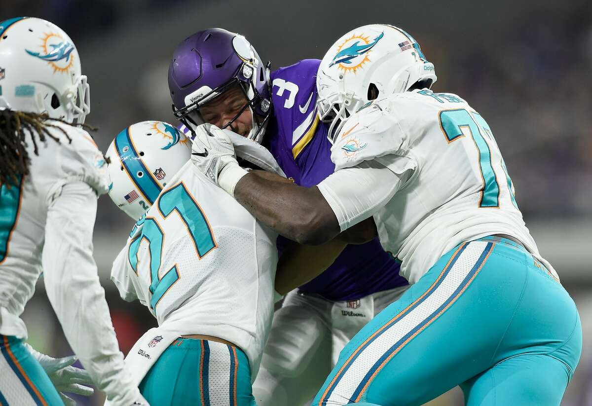 MINNEAPOLIS, MN - AUGUST 31: Jordan Lucas #21 and Jesse Davis #77 of the Miami Dolphins tackle Mitch Leidner #3 of the Minnesota Vikings during the third quarter in the preseason game on August 31, 2017 at U.S. Bank Stadium in Minneapolis, Minnesota. The Dolphins defeated the Vikings 30-9. (Photo by Hannah Foslien/Getty Images)