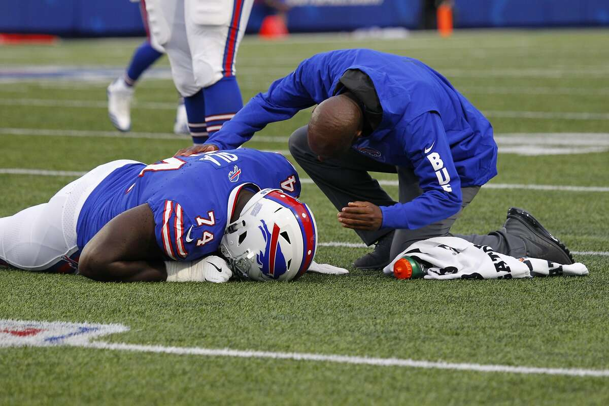 A trainer helps Buffalo Bills offensive tackle Michael Ola (74) after he is injured during the first half of a preseason NFL football game against the Detroit Lions Thursday, Aug. 31, 2017, in Orchard Park, N.Y. (AP Photo/Jeffrey T. Barnes)