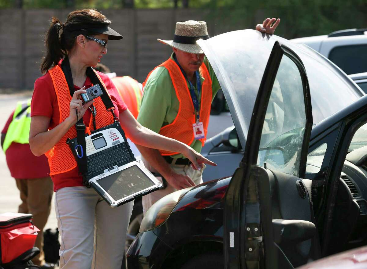 Husband and wife Automotive Claim Inspectors Clint and Shannon Allison take photographs of a Hurricane Harvey flooded car while working on estimations at a salvage yard north of Houston Friday, Sept. 1, 2017, in Houston. ( Yi-Chin Lee / Houston Chronicle )
