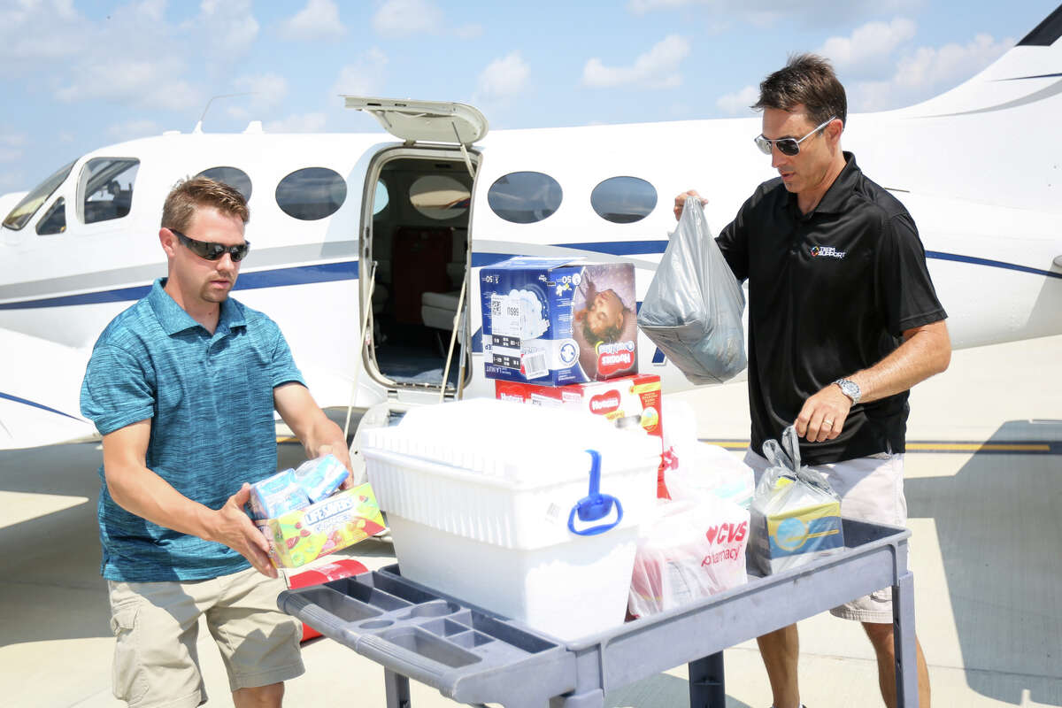 Volunteers Travis Forshee, left, and Robert Johnson, right, unload donations from a Cessna aircraft during Operation Air Drop on Friday at Conroe-North Houston Regional Airport.