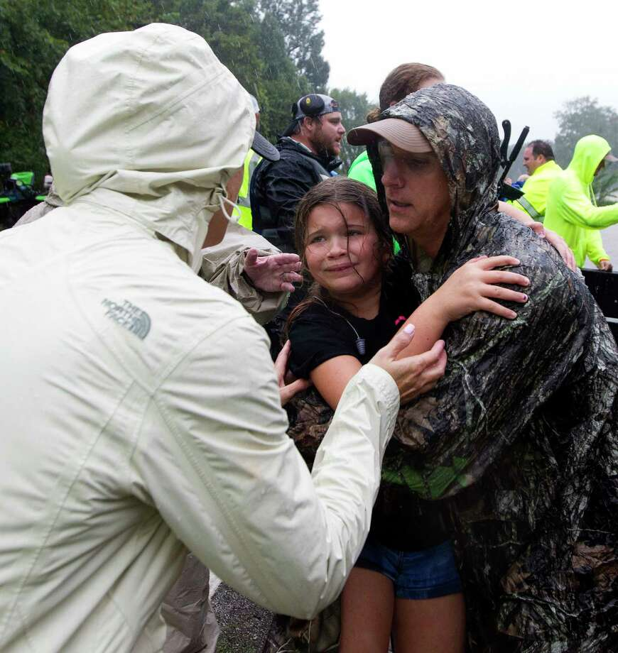 Taylor Jackson, 8, reacts as she is handed to her mom Alyssa after being evacuated from a home on FM 1485, Tuesday, Aug. 29, 2017, in New Caney. Photo: Jason Fochtman, Staff Photographer / Internal