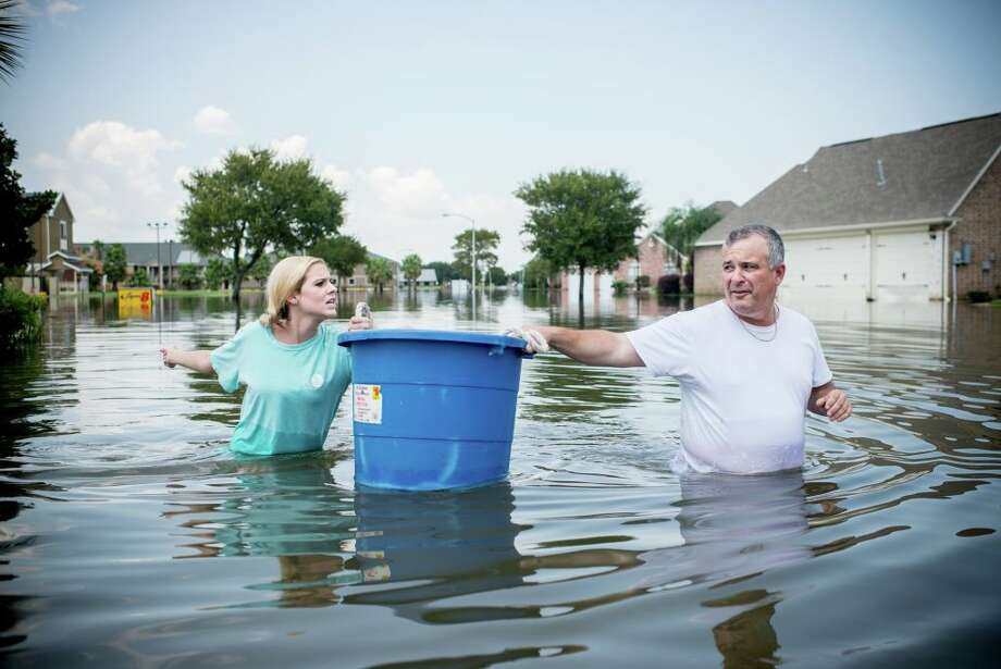 Jenna Fountain and her father, Kevin, float a bucket down Regency Drive to recover items from their flooded home in Port Arthur, Texas, Friday, Sept. 1, 2017. Photo: AFP Contributor/AFP/Getty Images