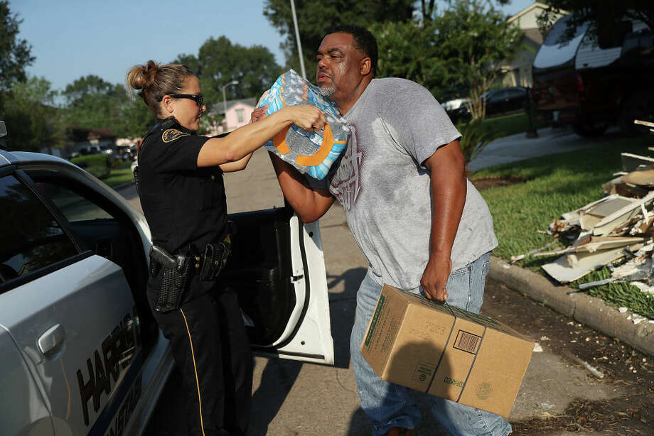 A Harrison County Sheriff gives out a box of MRE's and water to Casey Alfred as he begins the process of rebuilding after torrential rains caused widespread flooding during Hurricane and Tropical Storm Harvey on September 2, 2017 in Houston, Texas.  (Photo by Joe Raedle/Getty Images) Photo: Joe Raedle/Getty Images