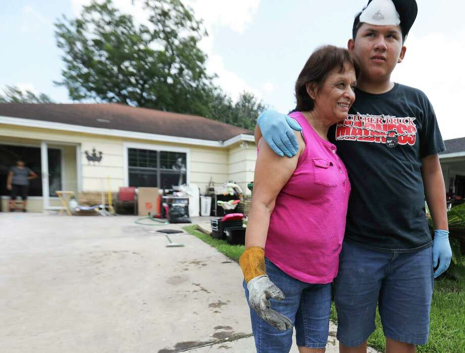 Sergio Torres hugs his grandmother, Eva Perez as they clean up both their homes that were damaged by Tropical Storm Harvey  on  Friday, Sept. 1, 2017, in Houston. Photo: Elizabeth Conley, Houston Chronicle / © 2017 Houston Chronicle