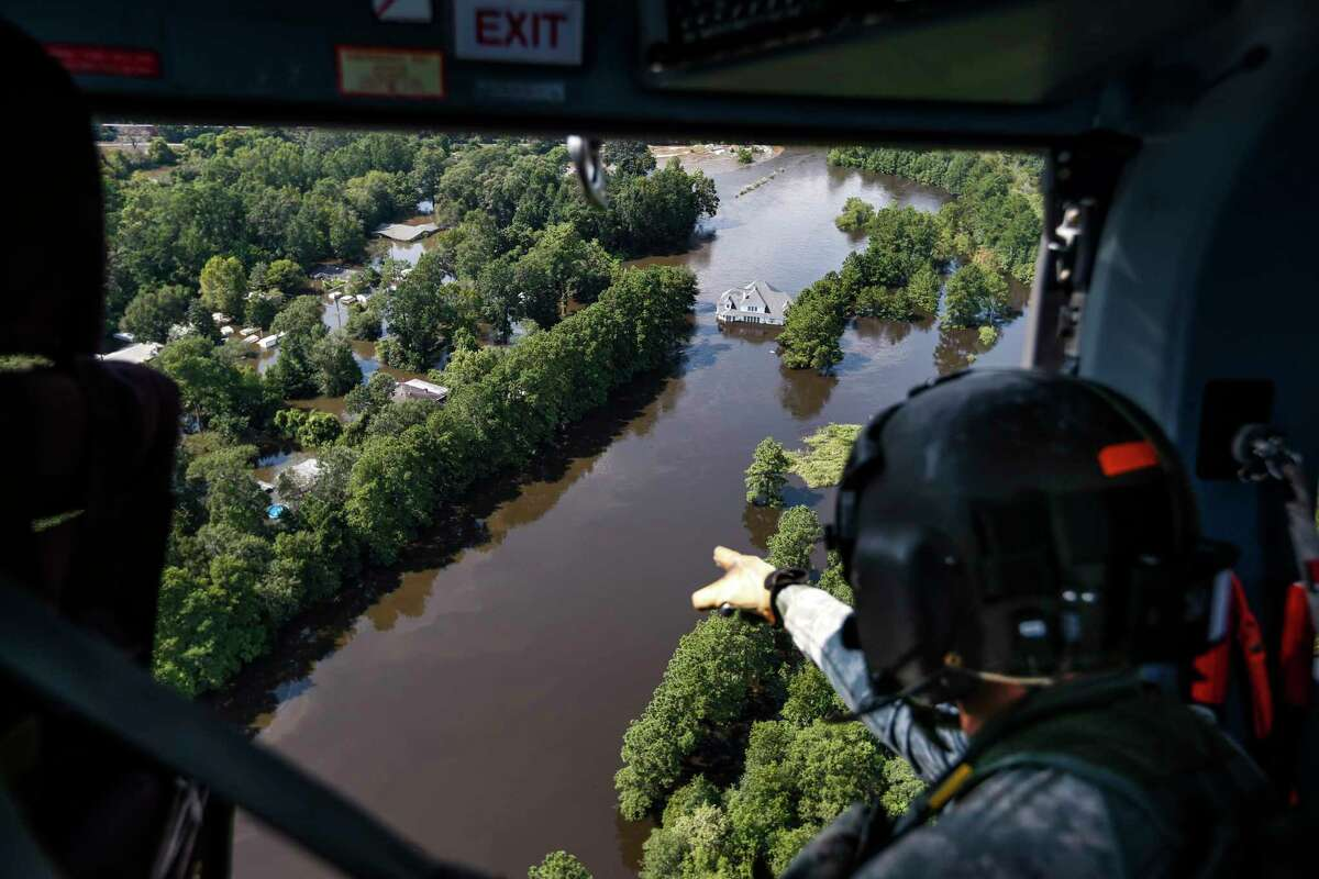 Sgt. Destry Riggs scans flooded areas during a search and rescue operation run by the 36th Combat Aviation Brigade of the Texas Army national Guard over areas hit by Tropical Storm Harvey on Friday, Sept. 1, 2017, north of Beaumont, Texas. Rural residents in flood areas should have their water wells tested before drinking the water, according to Texas A&M.