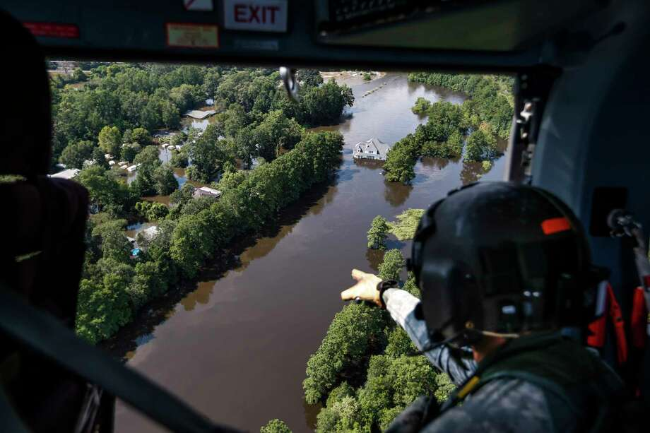 Sgt. Destry Riggs scans flooded areas during a search and rescue operation run by the 36th Combat Aviation Brigade of the Texas Army national Guard over areas hit by Tropical Storm Harvey on Friday, Sept. 1, 2017, north of Beaumont, Texas. Rural residents in flood areas should have their water wells tested before drinking the water, according to Texas A&M. Photo: Brett Coomer, Houston Chronicle / © 2017 Houston Chronicle