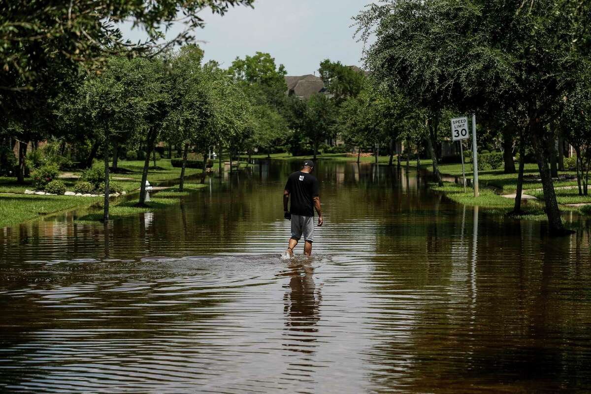 Ron Black walks down a flooded street to get to his house after Tropical Storm Harvey Friday, Sept. 1, 2017 in Sienna Plantation.