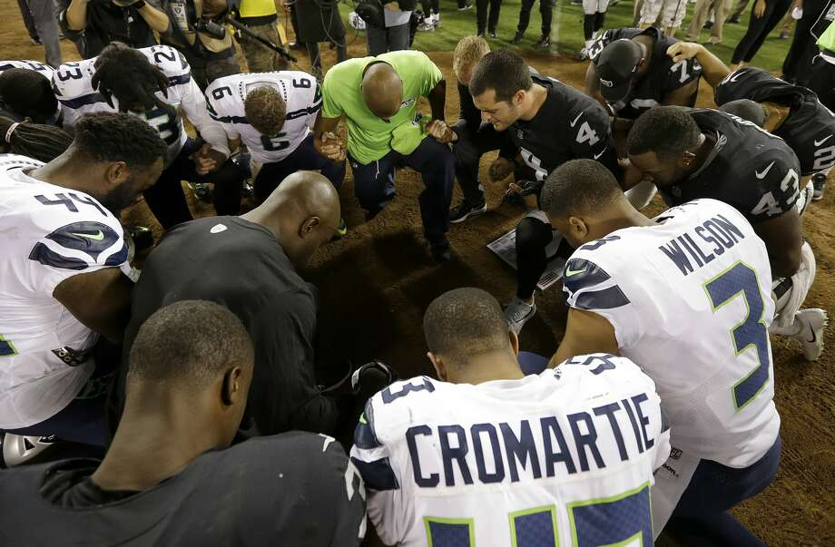Oakland Raiders and Seattle Seahawks players, including Marcus Cromartie (43), kneel in prayer after an NFL preseason football game in Oakland, Calif., Thursday, Aug. 31, 2017. (AP Photo/Ben Margot) Photo: Ben Margot/AP