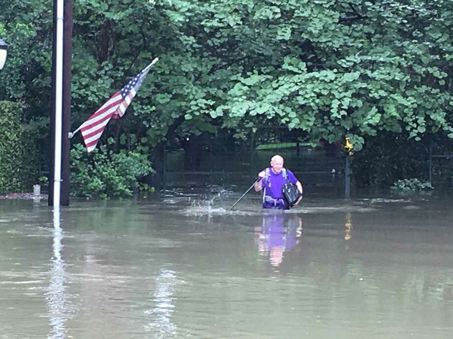 Former Mayor Bill White escapes from his home moments after it flooded on Sunday.