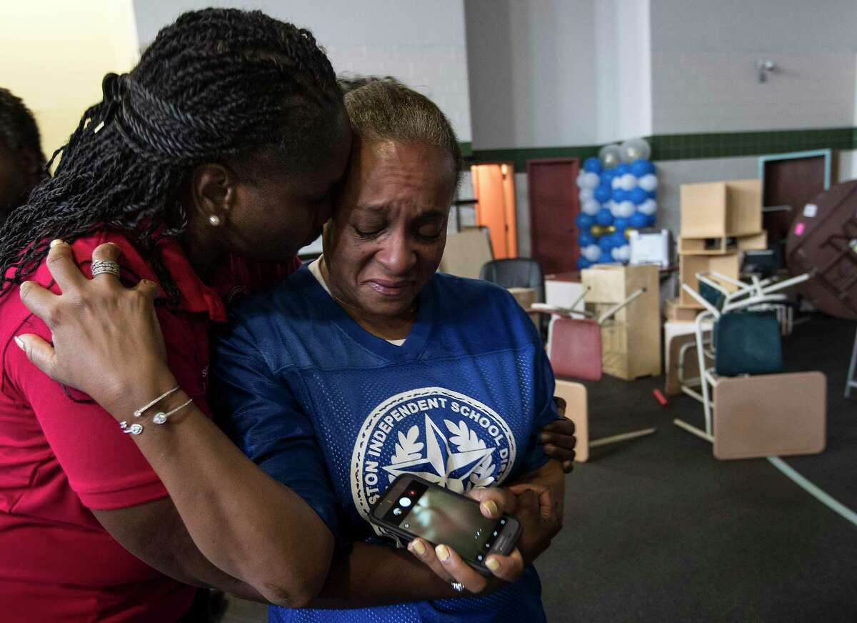 Houston Independent School District President Wanda Adams embraces Rhonda Skillern-Jones, HISD trustee, as they tour flood-damaged A.G. Hilliard Elementary School in the aftermath of Tropical Storm Harvey, on Saturday, Sept. 2, 2017, in Houston. See which Texas school districts most hurt by Harvey.