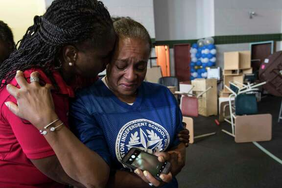 Houston Independent School District President Wanda Adams embraces Rhonda Skillern-Jones, HISD trustee, as they tour flood-damaged A.G. Hilliard Elementary School in the aftermath of Tropical Storm Harvey, on Saturday, Sept. 2, 2017, in Houston.