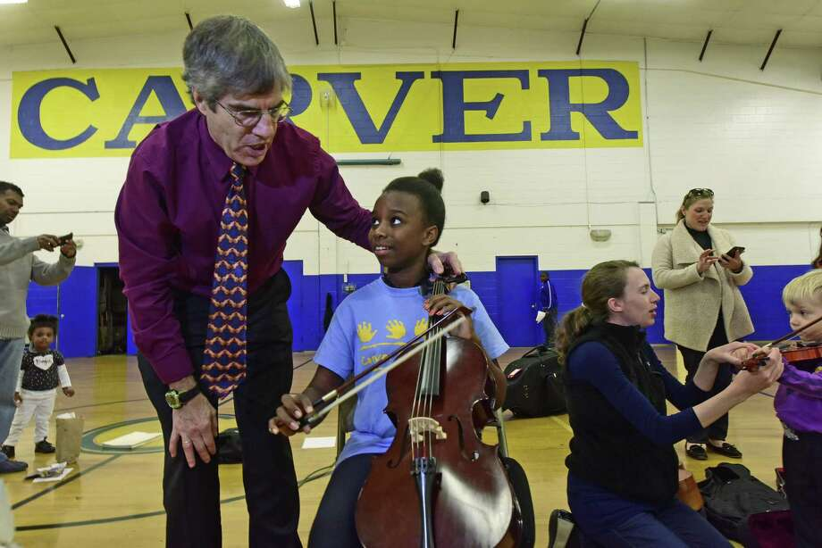 Principal cellist, Junar Sahlin, helps 11-year-old Witley Thermador with an instrument introduction during the Start With Strings presentation by Norwalk Symphony Orchestra musicians, Saturday, Oct. 15, 2016, at the George Washington Carver Center in Norwalk. Photo: Erik Trautmann / Hearst Connecticut Media / Connecticut Post