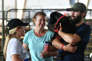 Michelle Lichtenberg, middle, looks Saturday at a dog that was rescued and dropped off at Ford Park's temporary animal shelter in Beaumont. The shelter is taking in animals displaced by Hurricane Harvey and handing out animal food. Erika Pearce and Nick Peacre from Annapolis are also pictured. Photo taken Saturday, September 02, 2017 Guiseppe Barranco/The Enterprise