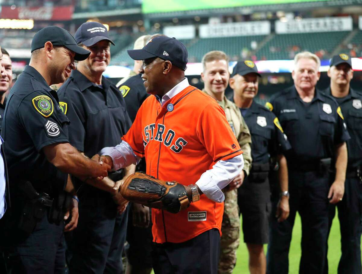 Houston Mayor Sylvester Turner shakes hands with first responders wearing a baseball glove before throwing out the first pitch before the start of an MLB baseball game at Minute Maid Park, Saturday, Sept. 2, 2017, in Houston. This is the first professional sporting event in the city since Tropical Storm Harvey.