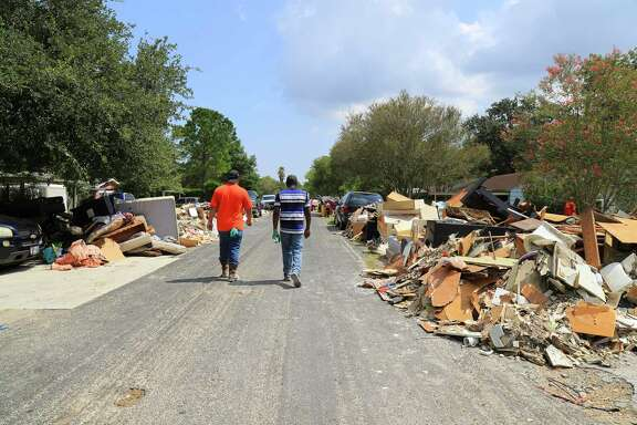 Piles of debris from waterlogged homes line Pecan Drive in Dickinson, Texas, Sept. 2, 2017. A week after Texas was slammed by Hurricane Harvey, this region was still engulfed in crisis on Saturday, with weary residents of Houston searching for ways to repair swamped homes and salvage possessions. (Jim Wilson/The New York Times)
