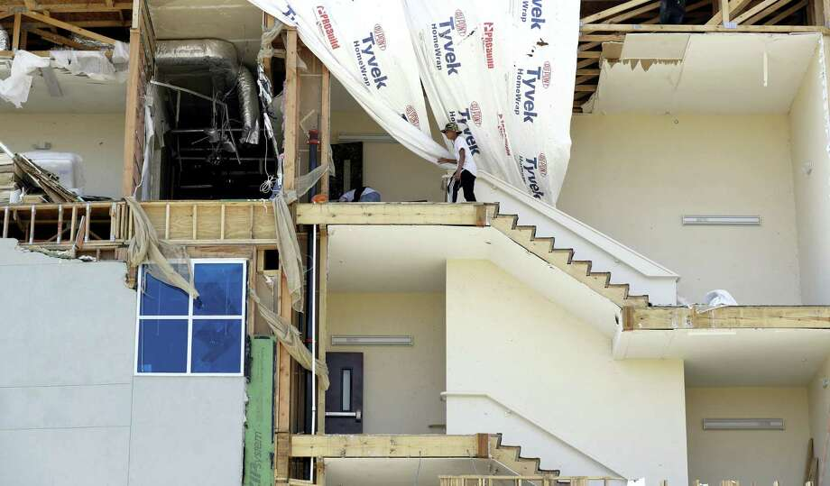 Workers pick up debris in a staircase of a four-story hotel exposed when the wall fell during Hurricane Harvey, Saturday, Sept. 2, 2017, in Rockport, Texas. Photo: AP Photo/Eric Gay / Copyright 2017 The Associated Press. All rights reserved.