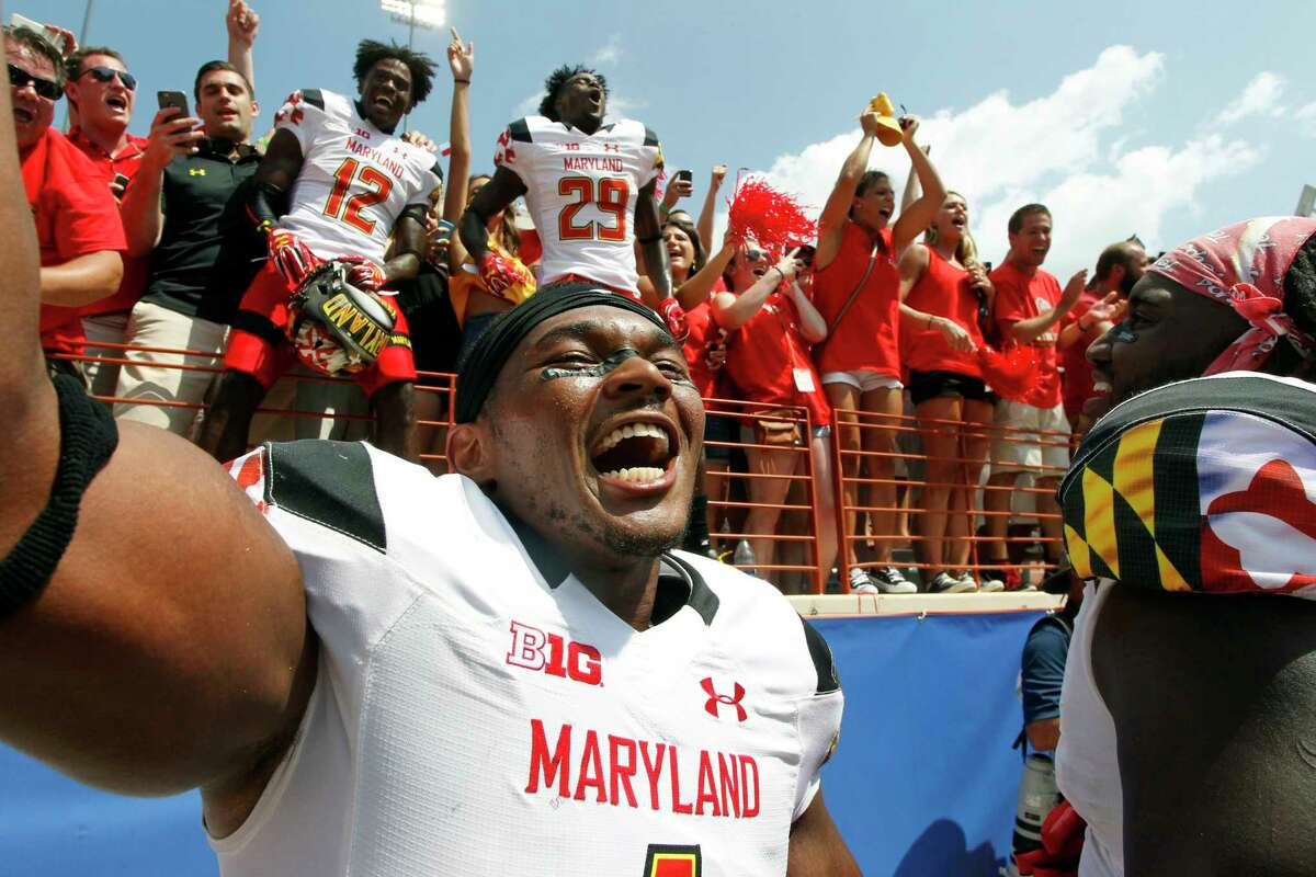 Maryland's Jermaine Carter, Jr. front, celebrates with teammates and fans after defeating Texas in an NCAA college football game, Saturday, Sept. 2, 2017, in Austin, Texas. Maryland won 51-41. (AP Photo/Michael Thomas)