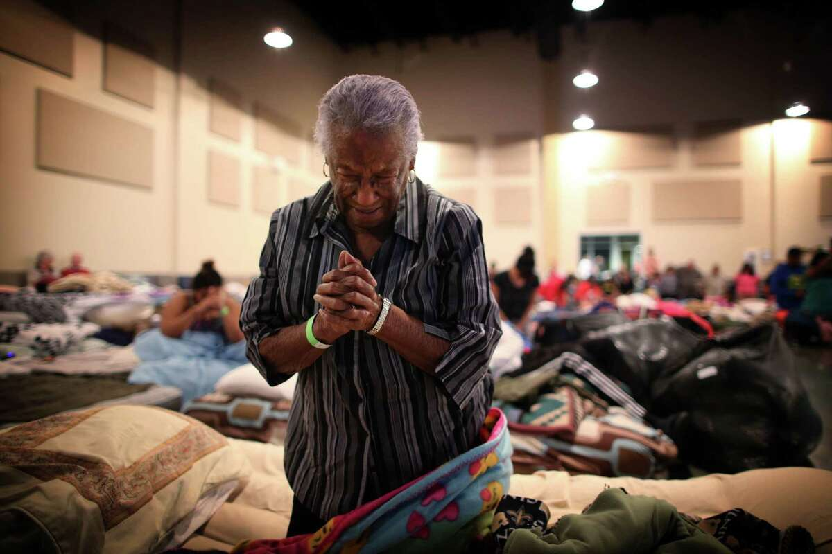Bernice Emerge, 80, says a tearful prayer at the Woodlands Church in The Woodlands, a suburb north of Houston, where some 200 evacuees were sheltering, Aug. 29, 2017. Tropical Storm Harvey made a second landfall in Louisiana early Wednesday morning, but the emergency was far from over in Texas, where beleaguered residents continued to struggle against rising floodwaters caused by six days of rainfall. (Barbara Davidson/The New York Times)