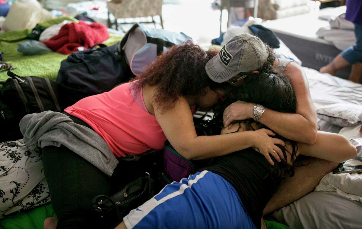 A family hugs upon their arrival at a shelter at St. Thomas Presbyterian Church in west Houston after Harvey on Tuesday Aug. 29, 2017. Their home was flooded out the night before. ( Jay Janner/Austin American-Statesman via AP)
