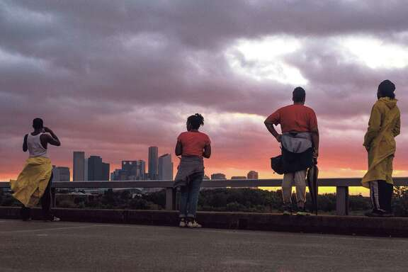 People stand on Hirsch Road to watch the sun sets over the Houston skyline as Tropical Storm Harvey moves out of the region Tuesday, Aug. 29, 2017. ( Michael Ciaglo / Houston Chronicle)