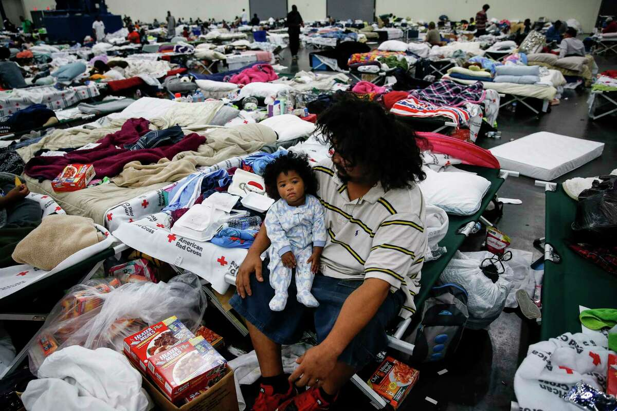 Edgar Molina holds his one-year-old daughter, Miracle Marie Molina, on a cot at the George R. Brown Convention Center where nearly 10,000 people are taking shelter after Tropical Storm Harvey Wednesday, Aug. 30, 2017 in Houston. Molina and his daughter have been at the shelter since Sunday. ( Michael Ciaglo / Houston Chronicle)