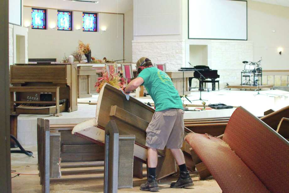 Church member William Sternberg wrestles with a soiled pew in the sanctuary at Dickinson First United Methodist Church on Saturday. The church was damaged by Hurricane Harvey. Photo: Kirk Sides / © 2017 Kirk Sides / Houston Chronicle