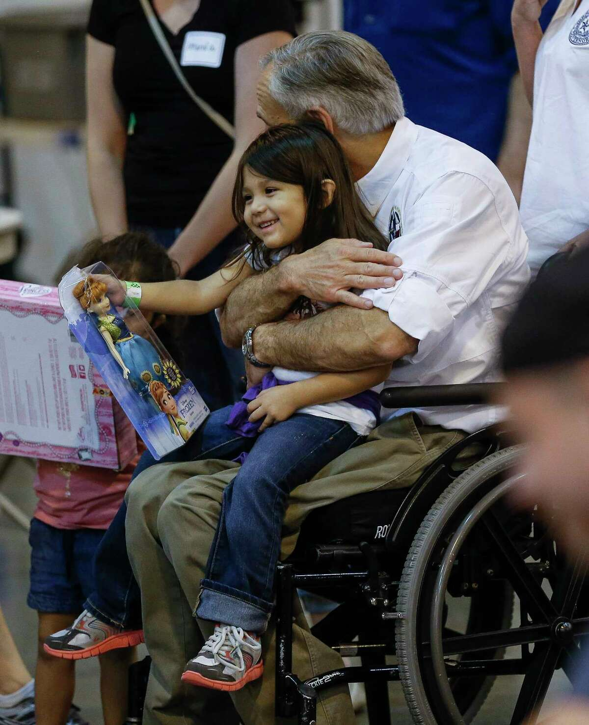 Texas Governor Greg Abbott hugs a child while visiting Tropical Storm Harvey evacuees at NRG Center in Houston Saturday, Sept. 2, 2017.