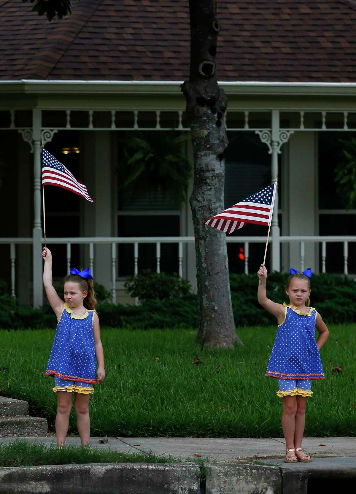Pearland residents wave American flags as President Donald Trump's motorcade passes through the neighborhood as he visits Houston in the wake of Tropical Storm Harvey Saturday, Sept. 2, 2017.