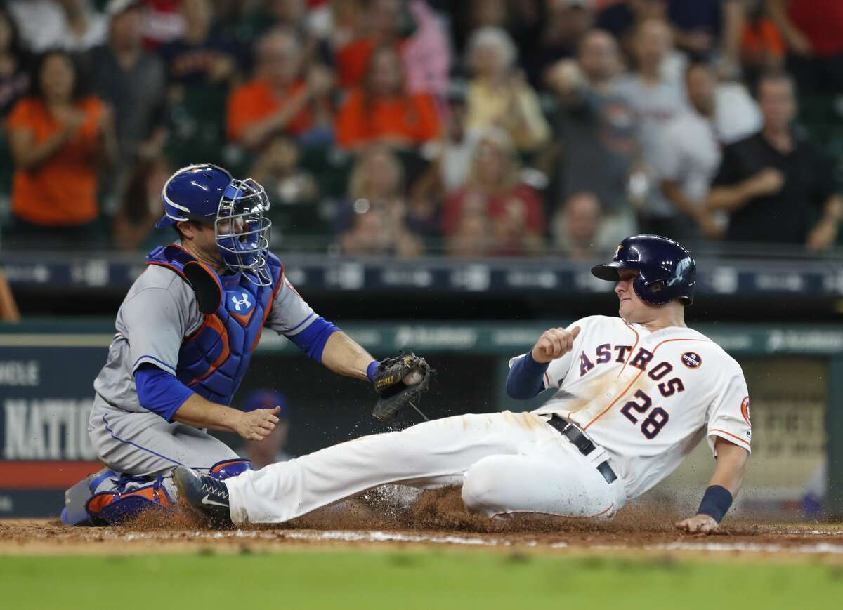 Houston Astros third baseman J.D. Davis (28) slides into home to score a run on a single by Tony Kemp in the seventh inning of an MLB baseball game at Minute Maid Park, Saturday, Sept. 2, 2017, in Houston. This is the first professional sporting event in the city since Tropical Storm Harvey. ( Karen Warren / Houston Chronicle )