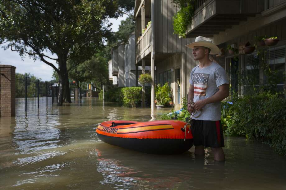 Mustafa Herby, originally from Iraq, stands outside his flooded condominium on Gessner near Brier Forest, Wednesday, Aug. 30, 2017, in Houston. After watching water flow into his own condo on Gessner north of Brier Forest, Mustafa spent the beginning of the week swimming through flood waters to evacuate his fellow Houstonians from their flooded homes on an orange raft he had bought on a whim back when he was living in Syria. (Mark Mulligan / Houston Chronicle) Photo: Mark Mulligan/Mark Mulligan / Houston Chronicle
