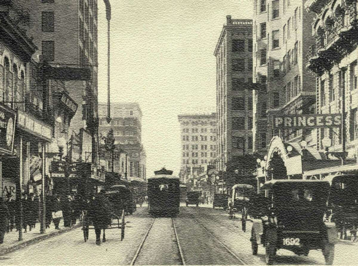 A streetcar shares Houston Street with automobiles and horse-drawn buggies.