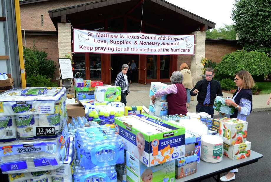 Shelley Lepetich, right, drops off bottles of water as St. Matthew's Church takes donations for Hurricane Harvey relief to fill one of two rental trucks at the church parking lot in Norwalk, Conn. on Saturday Sept. 2, 2017. Msgr. Walter Orlowski is driving one of the two trucks down to Our Lady of Guadalupe, the church's adopted Parish in Rosenberg, Texas. Photo: Christian Abraham / Hearst Connecticut Media / Connecticut Post