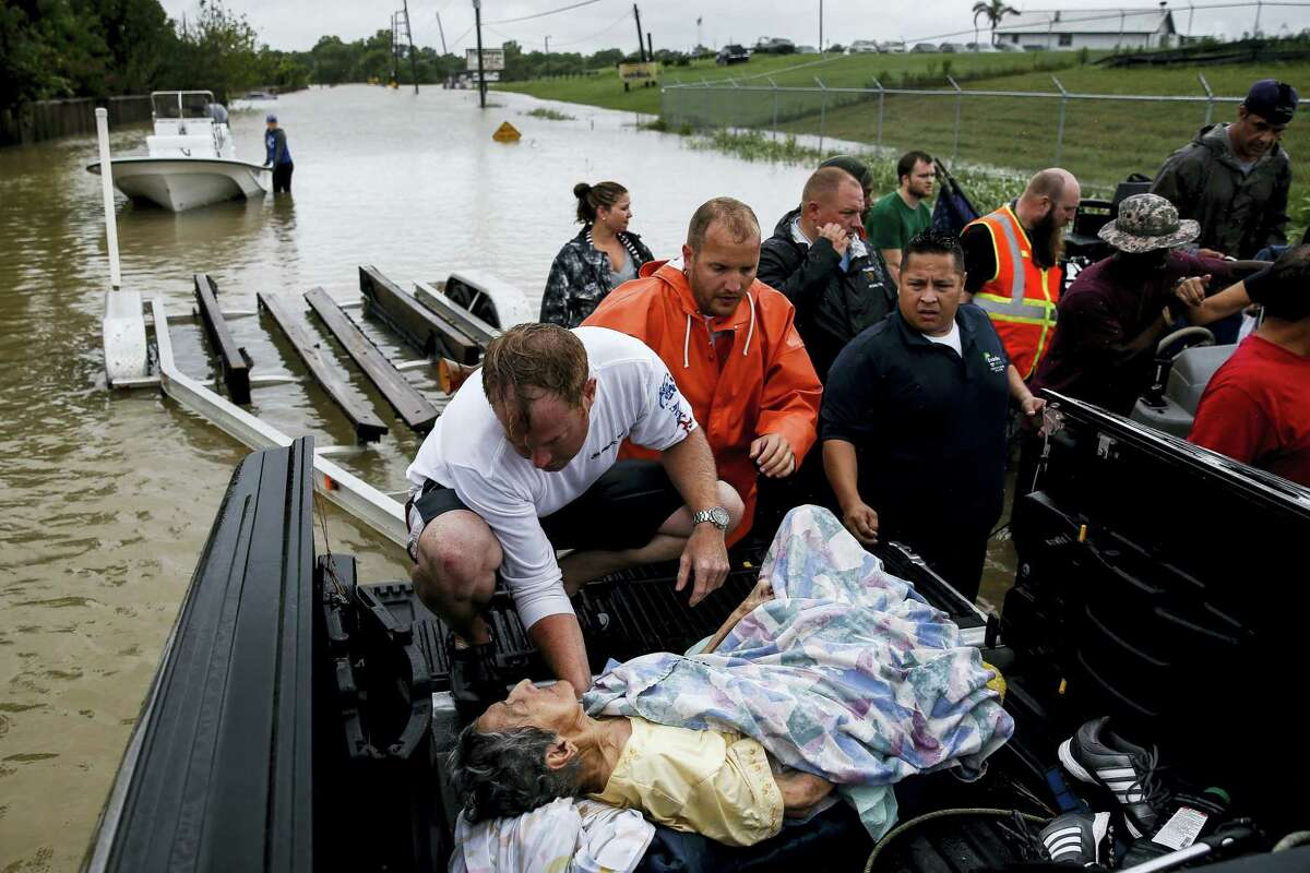 A rescuer moves Paulina Tamirano, 92, from a boat to a truck bed as people evacuate from rising waters from Tropical Storm Harvey in Houston.