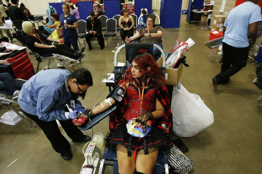 Alia Reed (center) dressed as Risa Koizumi from the anime, Lovely Complex, gets her blood drawn from phlebotomist Crystal Valdez at San Japan on Saturday, Sept. 2, 2017. San Antonio's big anime and Japanese pop culture convention celebrates its 10th year anniversary with a Labor Day Weekend full of costumed convention goers and much more geeky fun at the Convention Center. (Kin Man Hui/San Antonio Express-News) Photo: Kin Man Hui /San Antonio Express-News / ©2017 San Antonio Express-News