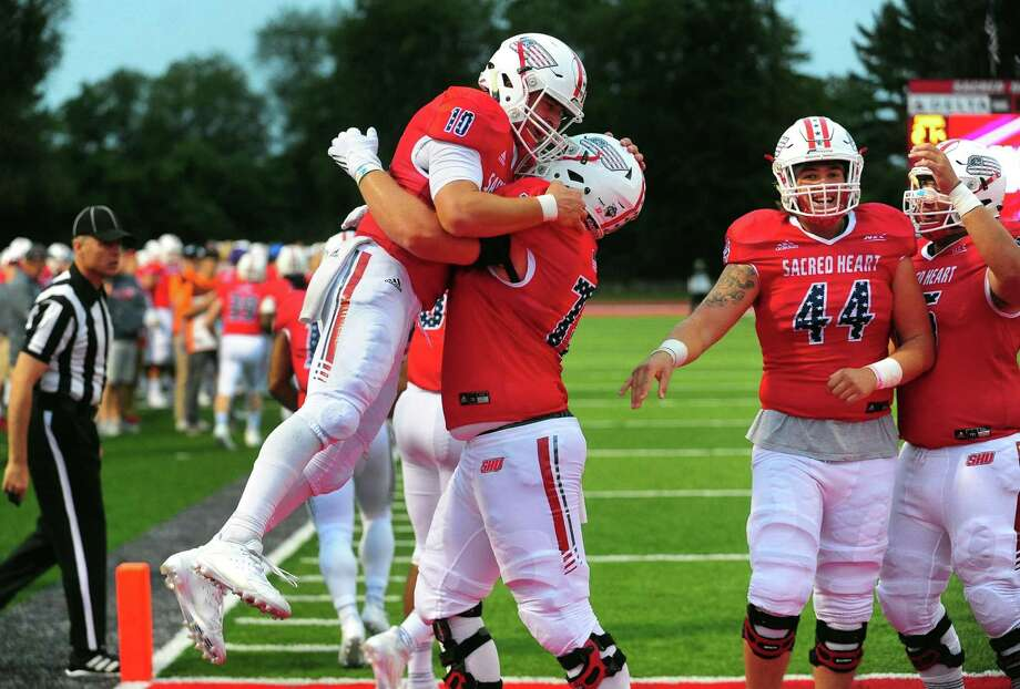 Sacred Heart University QB Kevin Duke (10) celebrates with teammate Andrew Star (72) after scoring a touchdown against Stetson in the season opener on Saturday in Fairfield. Photo: Christian Abraham / Hearst Connecticut Media / Connecticut Post