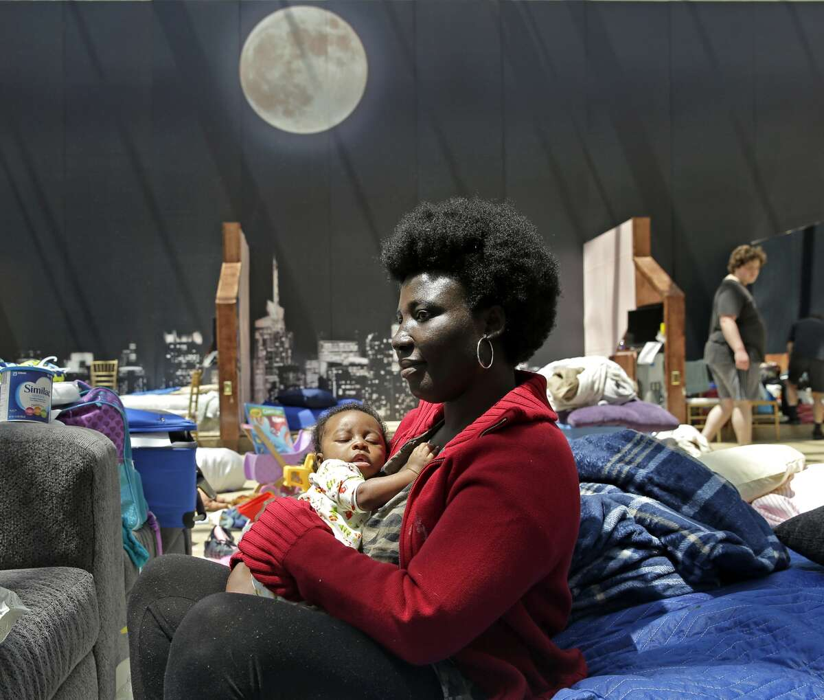 Gladys Dasi holds her two-month-old son Elliott while sheltering at Gallery Furniture Wednesday, Aug. 30, 2017, in Richmond, Texas. Dasi with her husband and four kids evacuated their Richmond home Sunday after it flooded as a result of Hurricane Harvey. The furniture store opened as a shelter housing as many as 350 people in an area being constructed as a museum of American industry. (AP Photo/Charlie Riedel)