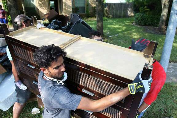 Baquir Ali, front, is among Houstonians working with locally organized volunteer groups to help flood victims.