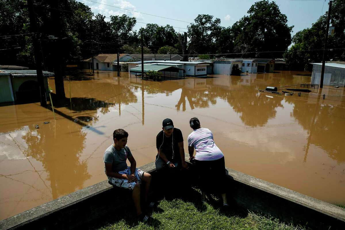 Rosalinda Gomez, right, peers down Damon Street in Richmond as the flooded Brazos River runs through the neighborhood. The floodwaters give mosquitoes ample places to lay their eggs.