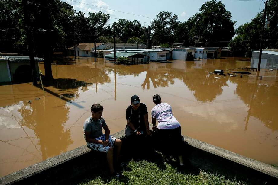 Rosalinda Gomez, right, peers down Damon Street in Richmond as the flooded Brazos River runs through the neighborhood. The floodwaters give mosquitoes ample places to lay their eggs. Photo: Michael Ciaglo, Staff / Michael Ciaglo